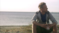 A man resting after jogging on the beach, Malmo, Sweden. Stock Footage