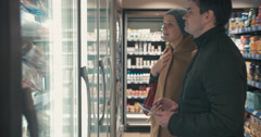 Young couple taking frozen food from fridge in the shop Stock Footage