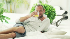 Portrait of happy man raising toast to camera on bed on patio HD Stock Footage