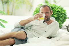 Portrait of happy man raising toast to camera on bed on patio NTSC Stock Footage