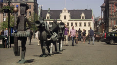 Two men passing by a statue in Malmo, Skane, Sweden. Stock Footage