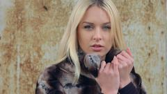A young beautiful blonde in an expensive fur in the background. Model video Stock Footage