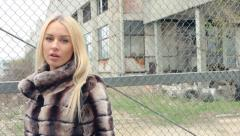 Stylish blond girl with bright makeup, in a luxurious fur coat abruptly turns Stock Footage