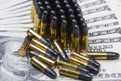 ammunition from the gun on 100 dollar bills - stock photo