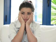 Portrait of sad, unhappy woman sitting on sofa at home NTSC - stock footage