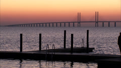 Two persons walking on a jetty in front of Oresundsbron, Malmo, Sweden. Stock Footage