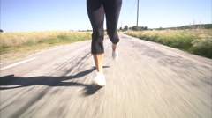 The legs of a woman jogging next to a corn field, Sweden. Stock Footage