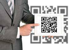 Businessman holding QR-code - stock photo