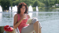 A woman on a jetty reading a book, Sweden. Stock Footage