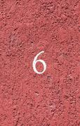 House number 6 at red wall Stock Photos