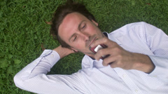 A man resting in a park using a mobile phone, Sweden. Stock Footage