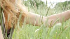 Beautiful blond Caucasian girl playing with grass and plants in slow motion 1 Stock Footage