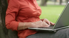 A woman in a park using a laptop, Sweden. Stock Footage