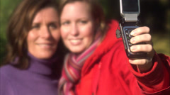Mother and daughter taking a picture using a mobile phone, Sweden. Stock Footage
