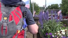 4K Tourists Walk Along Flag Filled Sidewalk - stock footage