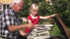 Girl and senior man recycling newspapers, Sweden. Stock Footage