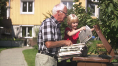 Granddaughter and grandfather recycling newspapers, Sweden. Stock Footage