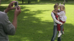 Woman, senior man and girl taking photographs in a park, Sweden. Stock Footage