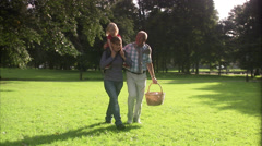 Senior man and young woman carrying a child on her shoulders, walking in a park, Stock Footage