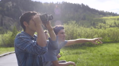 Teenage Boys Sit On A Boardwalk And Use Binoculars To Spot Wildlife - stock footage