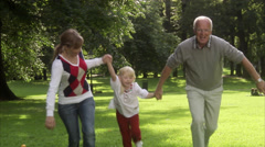 Senior man, young woman and a child playing in a park, Sweden. Stock Footage