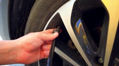 Hand and car wheel add air pressure Stock Footage