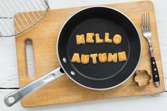 Cookie biscuits word HELLO AUTUMN in frying pan - stock photo