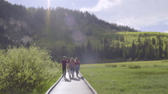 Group Of Friends Walk Along A Boardwalk In The Distance (Slow Motion) Stock Footage