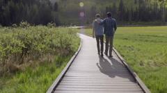 Best Friends Walk Down Boardwalk Toward Lake, Boy Puts Hand On His Friend's Back Stock Footage