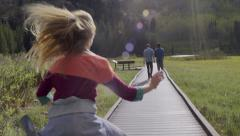 Teenage Boys Walk Along Boardwalk, Girl Runs To Catch Up, Puts Arms Around Them Stock Footage