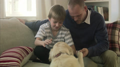 Father and son sitting in a sofa with a dog, Sweden. - stock footage
