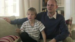 Father and son sitting in a sofa with a dog, Sweden. Stock Footage
