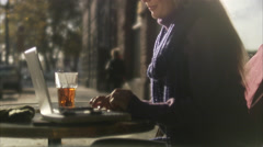 Young woman sitting in a cafe using a laptop, Sweden. Stock Footage