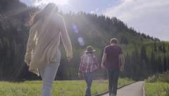 Teens Walk Along Boardwalk, Their Friends Run To Join Them, Couple Holds Hands Stock Footage