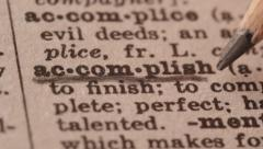 Accomplish - Fake dictionary definition of the word with pencil underline - stock footage