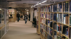 Students walking arm-in-arm in a library, Sweden. Stock Footage