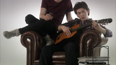Two teenage boys playing the guitar. Stock Footage