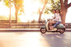 Cheerful young couple riding a scooter and having fun. Sun is shining in the  Stock Photos