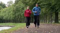 Couple jogging alongside a canal, Sweden. Stock Footage