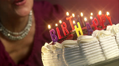 Woman blowing out the candles on a birthday cake, Sweden. Stock Footage