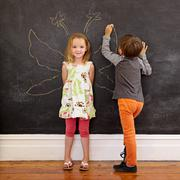 Little girl in front of a blackboard with boy drawing angel wing - stock photo