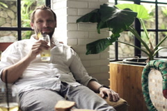 Handsome man raising toast to camera and drinking beverage in bar NTSC Stock Footage