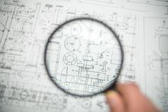 The loupe (magnifier) look through by blueprints engineering project background Stock Photos