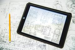 The blueprints engineering for the project near tablet (ipod) and pencil - stock photo