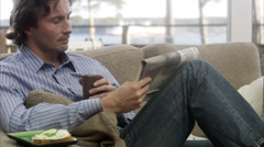 MS PAN Man sitting on sofa reading newspaper and drinking coffee / Liding_,  Stock Footage