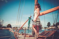 Stylish wealthy woman on a luxury wooden regatta Stock Photos
