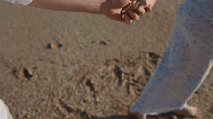 Young caucasian couple walk on the beach Stock Footage