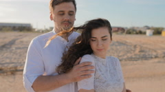 Caucasian young man and woman cuddle on the beach Stock Footage