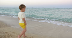 Boy Standing in the Incoming Waves Stock Footage