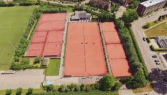 4K Drone shot of orange tennis courts in the summer - stock footage